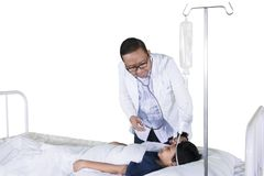 Il pediatra controlla la temperatura paziente sullo studio fotografia stock