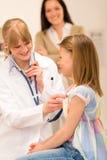 Il pediatra esamina la cassa della ragazza con lo stetoscopio Immagine Stock