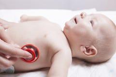 Il pediatra esamina tre mesi di neonato che per mezzo di uno stetoscopio Fotografie Stock