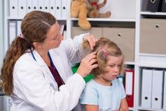 Il pediatra femminile in cappotto bianco del laboratorio ha esaminato il piccolo paziente immagine stock
