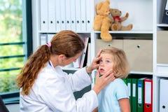 Il pediatra femminile in cappotto bianco del laboratorio ha esaminato il piccolo paziente fotografia stock libera da diritti