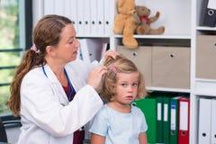 Il pediatra femminile in cappotto bianco del laboratorio ha esaminato il piccolo paziente FO fotografie stock libere da diritti
