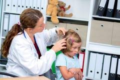 Il pediatra femminile in cappotto bianco del laboratorio ha esaminato il piccolo paziente immagine stock libera da diritti