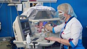 Il pediatra femminile controlla un bambino, facendo uso della macchina d'esplorazione video d archivio