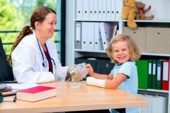 Il pediatra femminile ha candys per una bambina fotografia stock