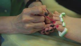 Il pedicure del primo piano dipinge le unghie del piede della giovane donna stock footage