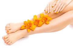 Il pedicure ed il manicure con un giglio arancio fioriscono Immagini Stock