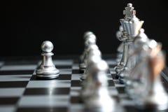 Il pegno d'argento è sul primo movimento nel gioco di scacchi su fondo nero immagine stock libera da diritti