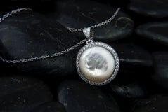 Il pendente dell'oro bianco con madreperla ed i diamanti sul nero lapida il backg Immagini Stock Libere da Diritti