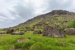 Il pendio di montagna verde sull'Islanda ha coperto da erba di grandi rocce in priorità alta Immagine Stock