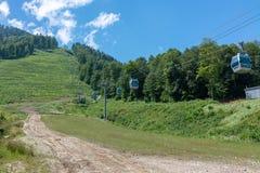 Il pendio verde della montagna con le cabine di funivia fotografia stock libera da diritti