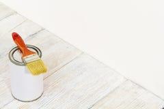 Il pennello e può, pennello e colore bianco sul pavimento di legno Immagine Stock