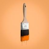 Il pennello ha caricato con colore arancio che gocciola fuori dalle setole Immagine Stock Libera da Diritti