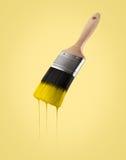 Il pennello ha caricato con colore giallo che gocciola fuori dalle setole Fotografia Stock