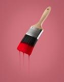 Il pennello ha caricato con colore rosso che gocciola fuori dalle setole Immagini Stock Libere da Diritti