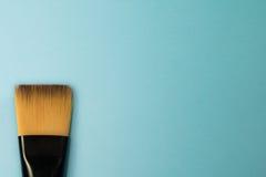 Il pennello piano artistico di concetto con i capelli naturali del nero rizza sul fondo blu del turchese Immagine Stock
