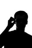 Il pensiero del giovane che tiene i vetri Immagine Stock Libera da Diritti