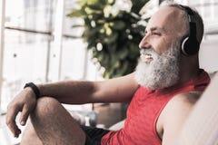 Il pensionato allegro sta godendo delle canzoni favorite mentre si sedeva sullo strato Fotografia Stock Libera da Diritti