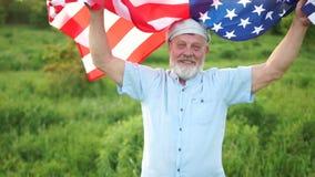 Il pensionato con la bandiera americana sulle spalle celebra la festa dell'indipendenza degli Stati Uniti, il giorno patriottico archivi video
