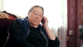Il pensionato della donna anziana parla sul telefono cellulare, teleobiettivo video d archivio