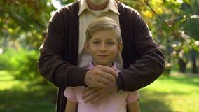 Il pensionato maschio che abbraccia il ragazzo, posante per la macchina fotografica, supporto della famiglia, ha assicurato l'inf stock footage