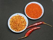 Il peperoncino rosso, peperone si sfalda e scoppio della polvere di peperoncino rosso fotografie stock
