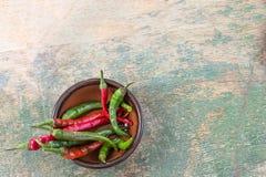 Il peperoncino rosso verde e rosso sul canestro di vimini sulla tavola di legno, ingrediente di erbe in molti generi di alimento  immagine stock libera da diritti