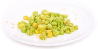 Il peperoncino verde ha tagliato nei pezzi su un fondo bianco immagine stock