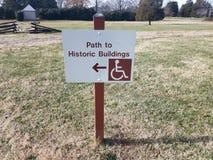 Il percorso ai monumenti storici firma con il simbolo della sedia a rotelle e della freccia immagini stock