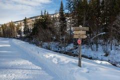 Il percorso di legno della direzione firma dentro la traccia di montagna innevata Fotografie Stock