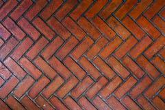 Il percorso pavimentato con il mattone rosso nel modello di zigzag, modello di pietra rosso di stile della spina di pesce del pas immagini stock