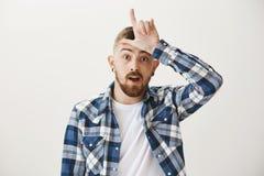 Il perdente è destino Il giovane fratello europeo bello nella rappresentazione normale blu della camicia perde il gesto sopra la  Fotografia Stock