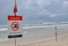 Il pericolo e segnale di pericolo lungo la parte anteriore della spiaggia Fotografia Stock