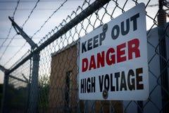 Il pericolo impedisce di entrare il segno ad alta tensione sul recinto del filo spinato Immagini Stock Libere da Diritti