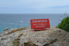Il pericolo nessun segno di accesso pubblico sul bordo della scogliera Fotografia Stock