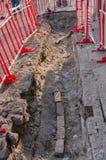 Il pericolo per i pedoni sulla via Un pozzo sul marciapiede, circondato dalle barriere d'avvertimento rosse e bianche Riparazione immagini stock
