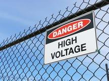 Il pericolo, segno ad alta tensione sul recinto con il fondo del cielo blu Fotografia Stock