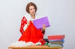 Il personale dell'ufficio della ragazza vestito come Santa Claus estrae una cartella dalla borsa per i regali alla tavola con fol Immagini Stock