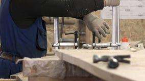 Il personale specialmente formato installa le prese basse di legno di un vice e perfino le avvita relè di scorrimento video d archivio