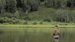 Il pescatore allegro sta pescando in acqua di fiume calma vicino alla riva archivi video