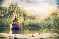 Il pescatore con le canne da pesca sta pescando in una barca di legno contro il fondo di bello natura e lago o fiume immagine stock