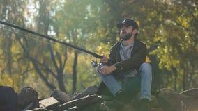 Il pescatore emozionante che fila pescando la bobina, ha pescato il pesce, tirante la barretta, felicità video d archivio