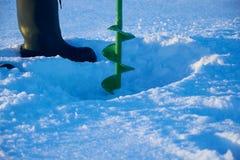 Il pescatore fa il foro in ghiaccio del lago Fotografia Stock Libera da Diritti