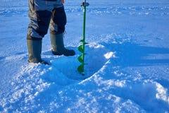 Il pescatore fa il foro in ghiaccio del lago Immagine Stock
