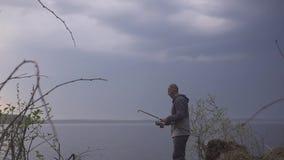 Il pescatore finisce di pescare sul lago di mattina, archivi video