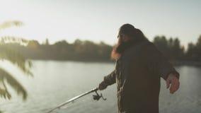 Il pescatore getta la barretta nel fiume Pescatore barbuto che pesca con la canna da pesca che sta sulla banca del fiume stock footage