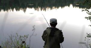 Il pescatore getta una canna da pesca sulla sponda del fiume video d archivio