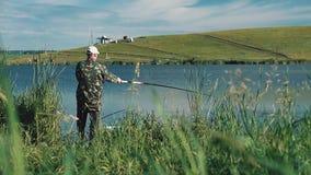 Il pescatore ha messo una linea fuori con una canna da pesca nel lago archivi video