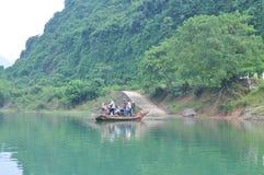 Il pescatore locale sta utilizzando la sua piccola barca come traghetto per trasferire la gente Immagine Stock