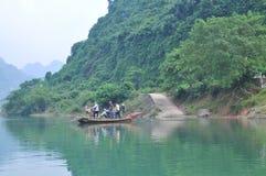 Il pescatore locale sta utilizzando la sua piccola barca come traghetto per trasferire la gente Fotografia Stock